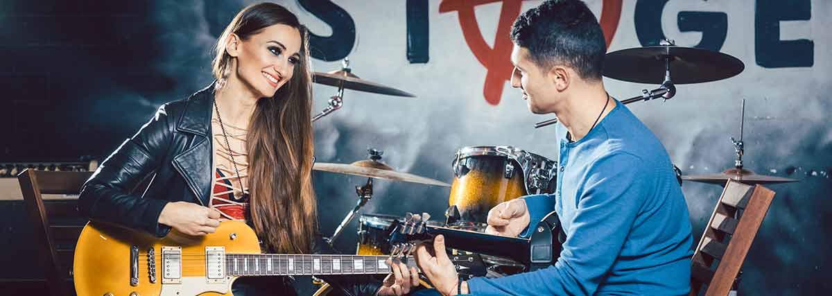 man teaching woman the guitar