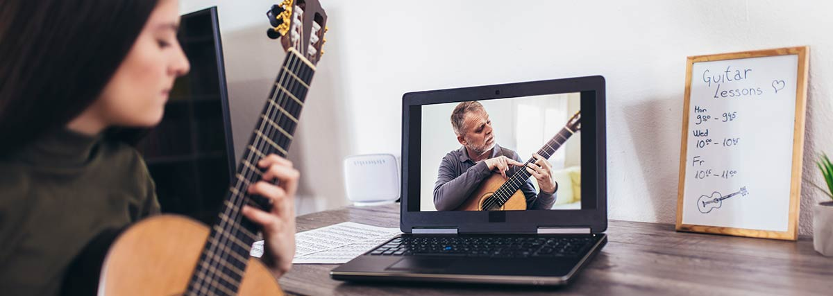 woman taking online guitar lesson